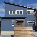 01:ブルーの外観と木の塀が目立ちながらも温かみ感じる雰囲気に仕上げています
