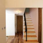3:グレーピンクの壁とスチール手すりの階段。階段下は収納として有効活用