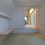 ④一段下がった和室。階段下になるスペースに布団収納を設け、引戸には紺色の和紙を使用。