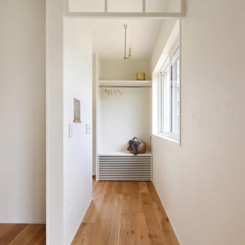玄関ホールに床下エアコンと上着掛け