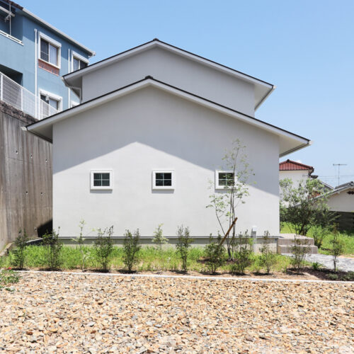淡いグレーの外壁に白い格子窓がシンプルに並ぶデザイン